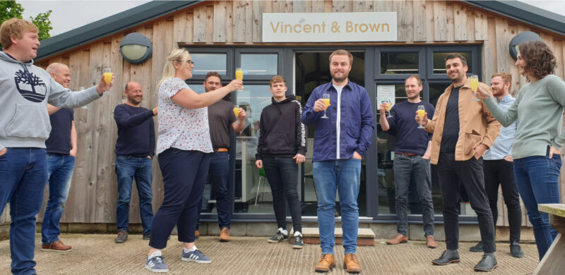 Team of architects holding up glasses to toast their colleague, who stands in the centre of the picture